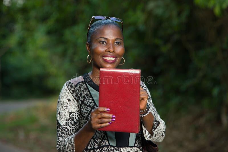 Mulher de sorriso apenas na natureza que guarda um livro imagens de stock royalty free