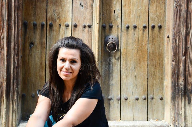 Mulher de sorriso assentada na frente da porta antiga foto de stock royalty free