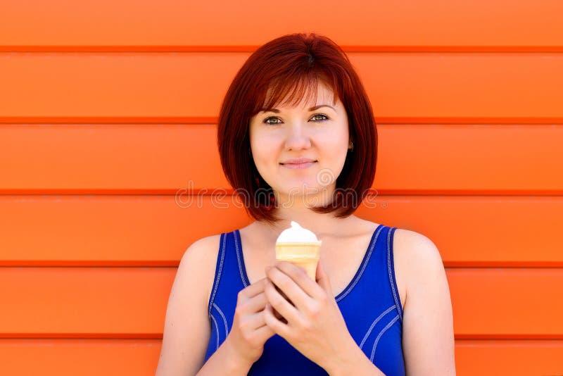 Mulher de sorriso atrativa com corte de cabelo do prumo e posição vermelha do cabelo no fundo alaranjado com gelado no cone do wa fotografia de stock royalty free