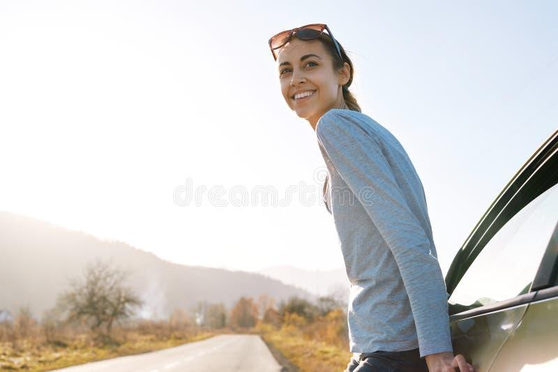 A mulher de sorriso atrativa está estando na estrada perto do carro fotos de stock royalty free