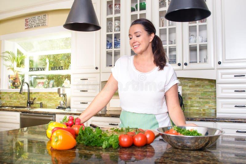 Mulher de sorriso atrativa que faz a salada em sua cozinha ensolarada imagens de stock royalty free