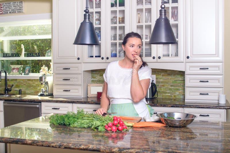 Mulher de sorriso atrativa que faz a salada em sua cozinha ensolarada fotos de stock royalty free