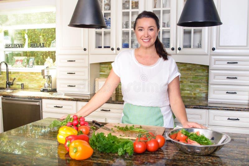Mulher de sorriso atrativa que faz a salada em sua cozinha ensolarada imagem de stock royalty free