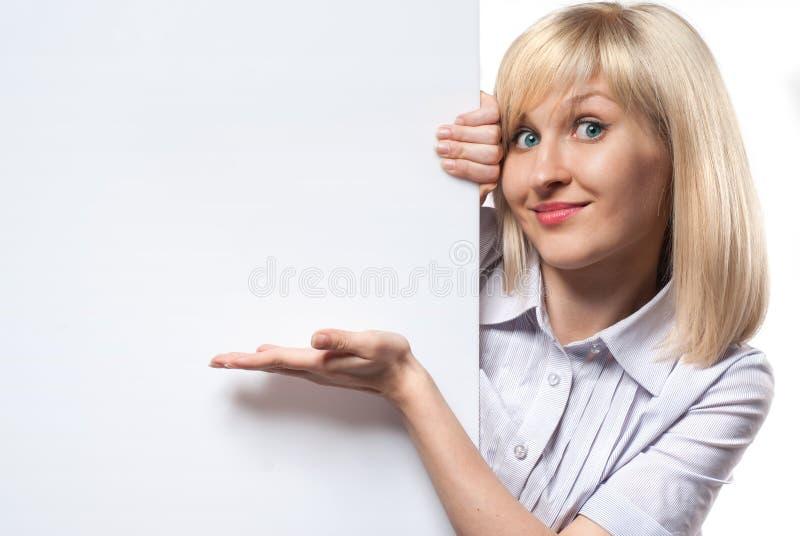 Mulher de sorriso atrativa que prende o papel vazio branco imagens de stock royalty free