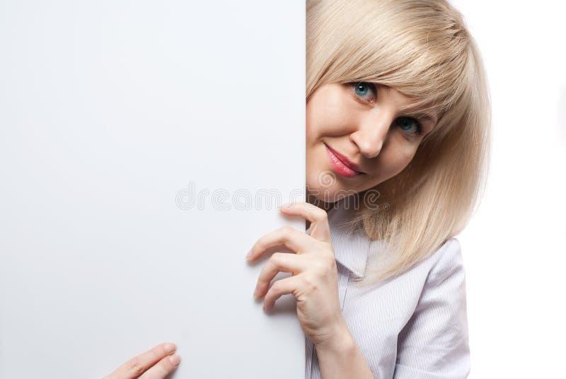 Mulher de sorriso atrativa que prende o papel vazio branco imagem de stock royalty free