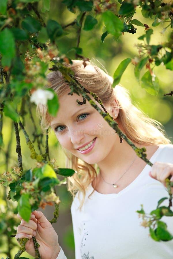 Mulher de sorriso através da árvore imagem de stock royalty free