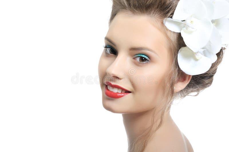 Mulher de sorriso bonita com as flores isoladas no branco fotografia de stock royalty free