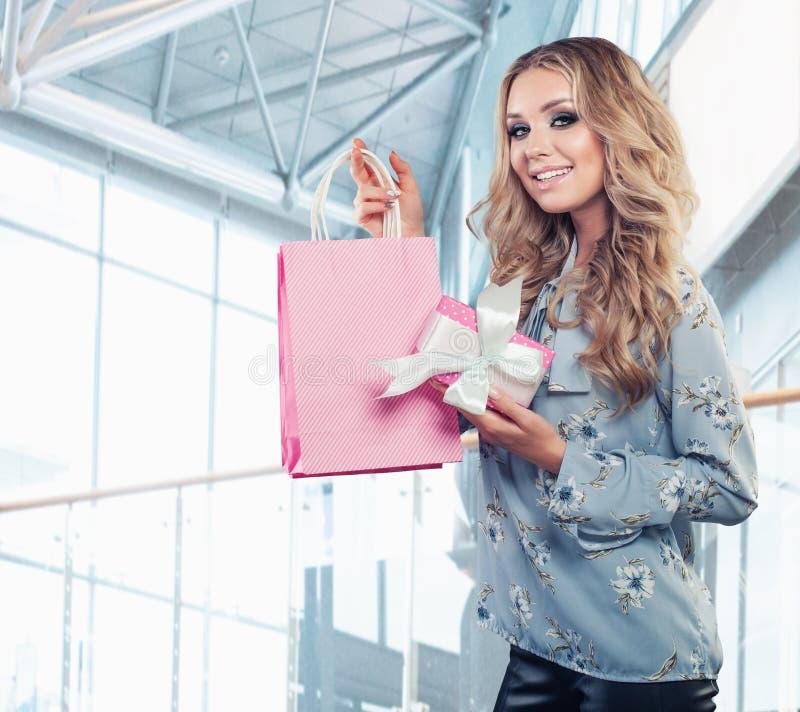 Mulher de sorriso bonita com caixa de presente e o saco de compras cor-de-rosa imagem de stock