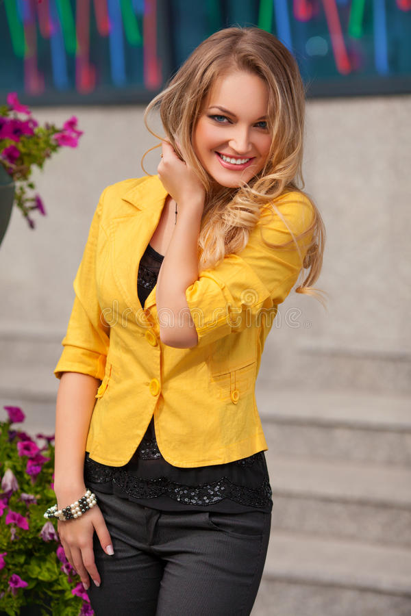 Mulher de sorriso bonita com o levantamento do revestimento amarelo e do cabelo louro exterior Menina da forma fotografia de stock