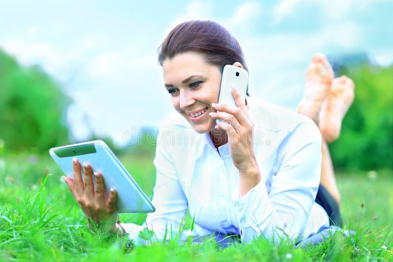 Mulher de sorriso bonita com PC da tabuleta e fala no telefone celular foto de stock royalty free