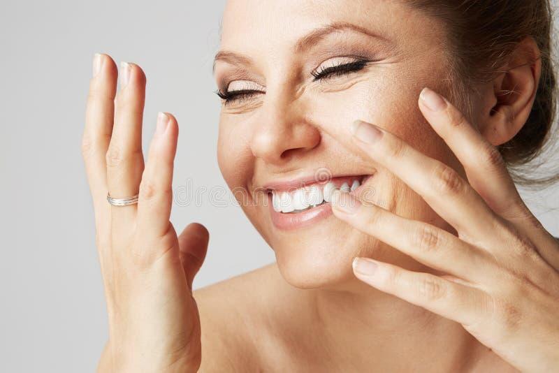 Mulher de sorriso bonita com pele limpa, composição natural, e os dentes brancos no fundo cinzento Feche acima do retrato médico foto de stock royalty free