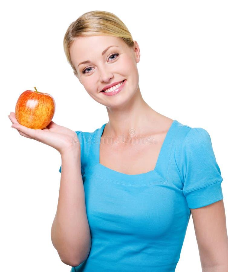 Mulher de sorriso bonita com uma maçã vermelha foto de stock royalty free