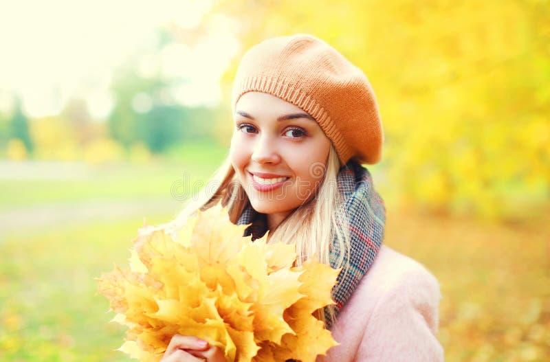 Mulher de sorriso bonita do retrato com as folhas de bordo amarelas no outono ensolarado morno fotografia de stock
