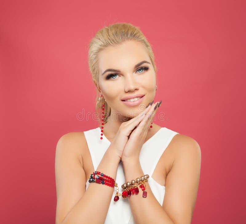 Mulher de sorriso bonita em braceletes do ouro com coral e em grânulos no fundo cor-de-rosa colorido fotografia de stock royalty free