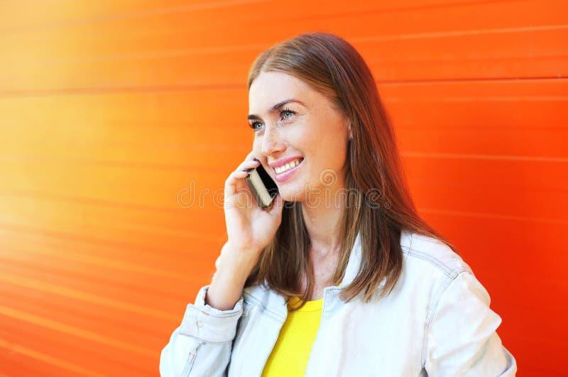 Mulher de sorriso bonita feliz do retrato que fala no smartphone imagem de stock