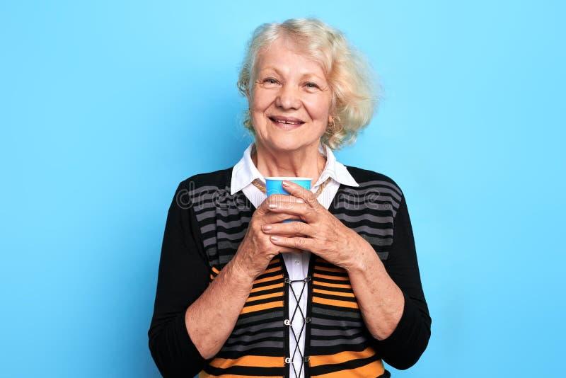 Mulher de sorriso bonita idosa que guarda um copo do chá e que olha a câmera fotos de stock royalty free
