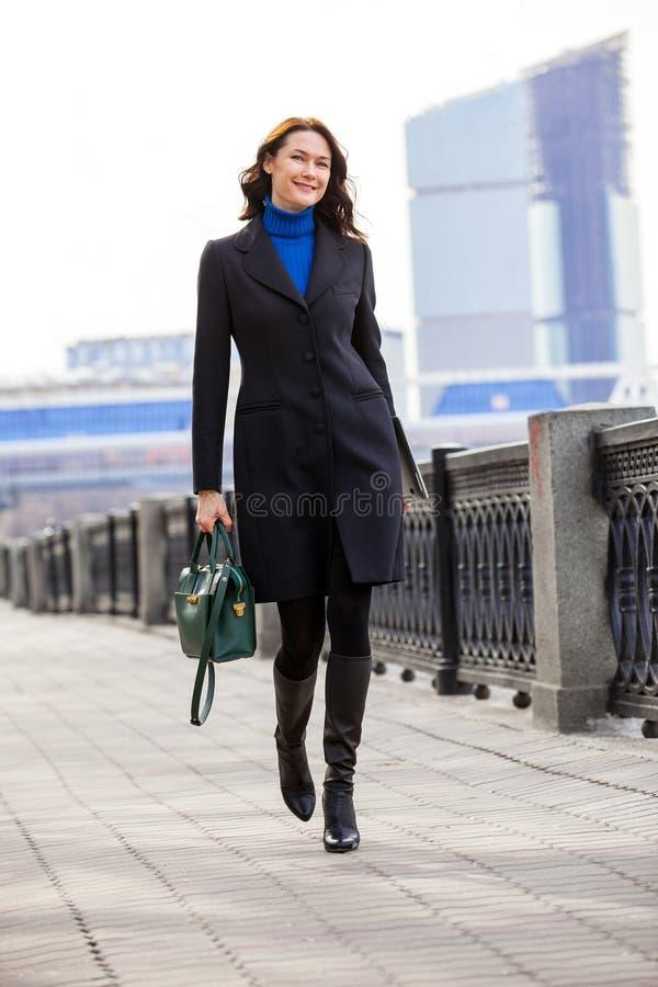 Mulher de sorriso bonita no revestimento escuro com bolsa e portátil imagens de stock
