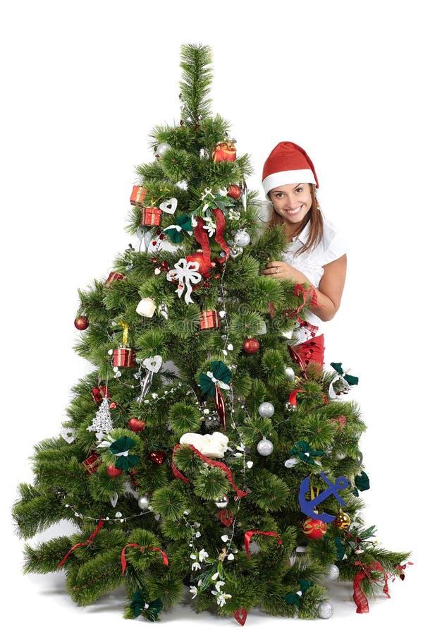 Mulher de sorriso bonita no tampão de Santa, atrás da árvore de Natal, isolada no branco imagem de stock