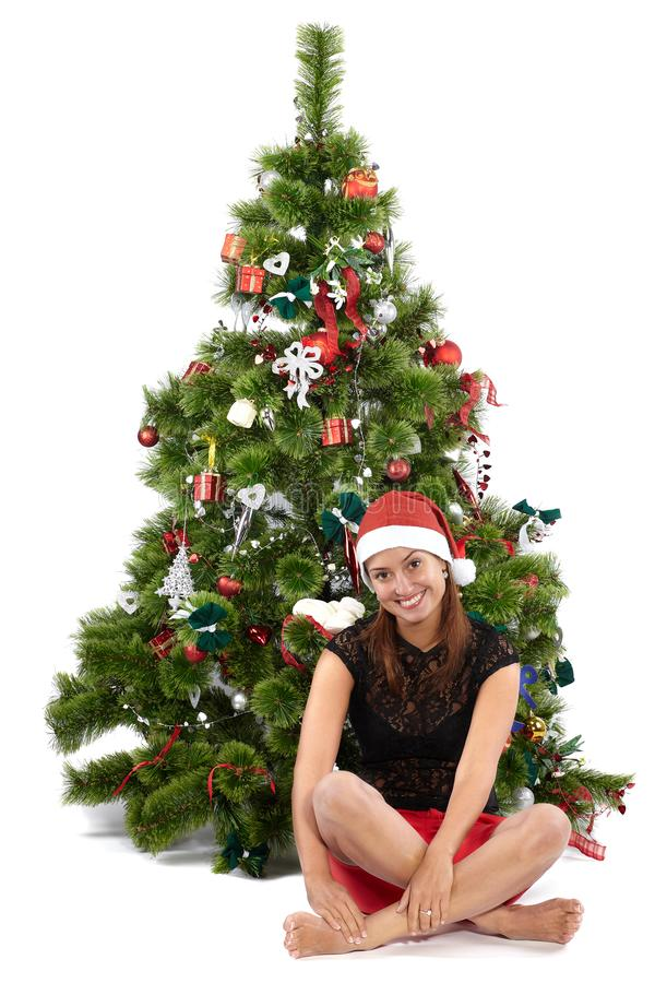 Mulher de sorriso bonita no tampão de Santa, sentando-se na frente da árvore de Natal imagem de stock