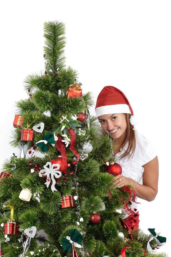 Mulher de sorriso bonita no tamp?o de Santa, atr?s da ?rvore de Natal, isolada no branco fotos de stock royalty free