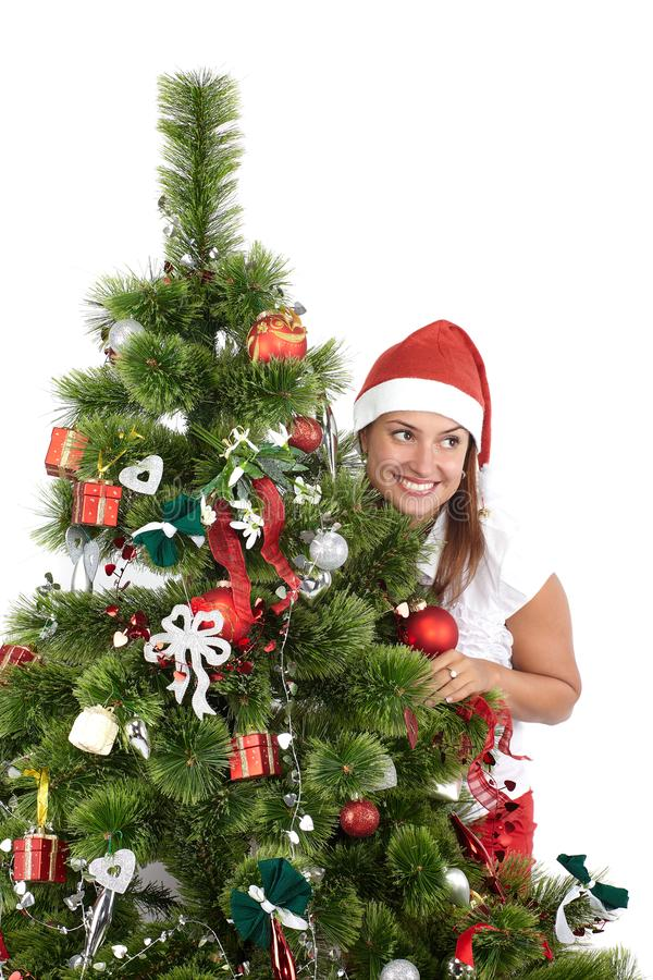 Mulher de sorriso bonita no tamp?o de Santa, atr?s da ?rvore de Natal, isolada no branco foto de stock
