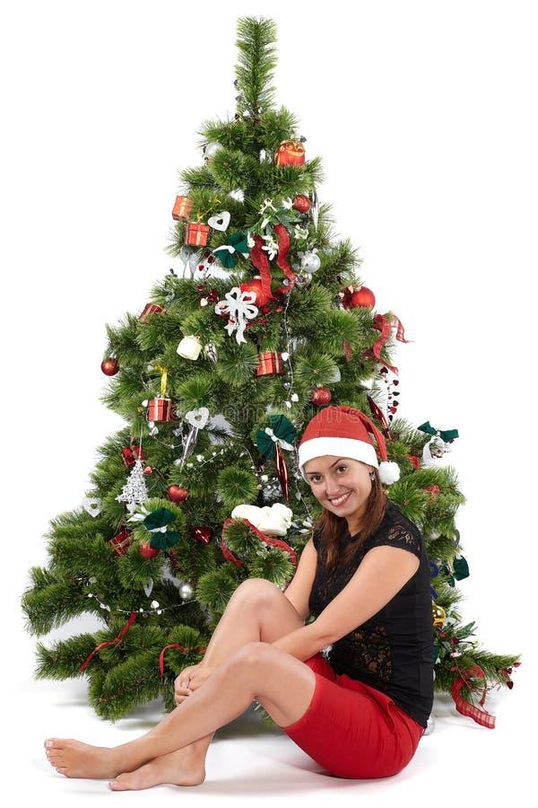 Mulher de sorriso bonita no tamp?o de Santa, na frente da ?rvore de Natal imagem de stock royalty free