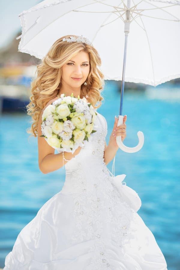 Mulher de sorriso bonita, noiva elegante com bouque das rosas do casamento fotografia de stock royalty free