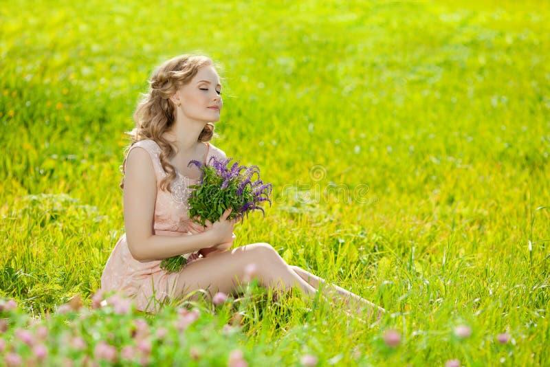 Mulher de sorriso bonita nova no campo, na grama Menina r foto de stock