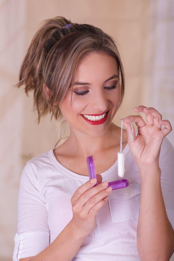 Mulher de sorriso bonita nova que guarda um tampão do algodão da menstruação em uma mão e com sua outra mão um roxo do plástico fotos de stock royalty free