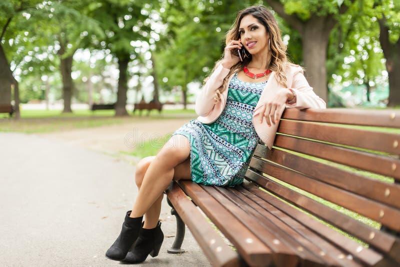 Mulher de sorriso bonita nova que usa telefones celulares no banco de parque fotos de stock royalty free