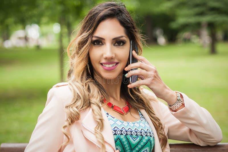 Mulher de sorriso bonita nova que usa telefones celulares no banco de parque fotografia de stock