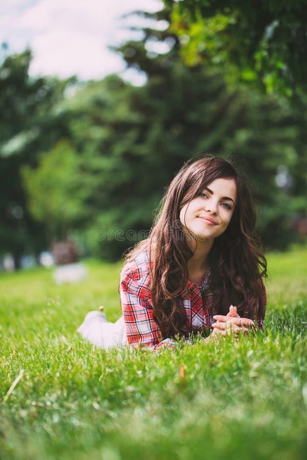 Mulher de sorriso bonita que encontra-se em uma grama exterior fotos de stock royalty free