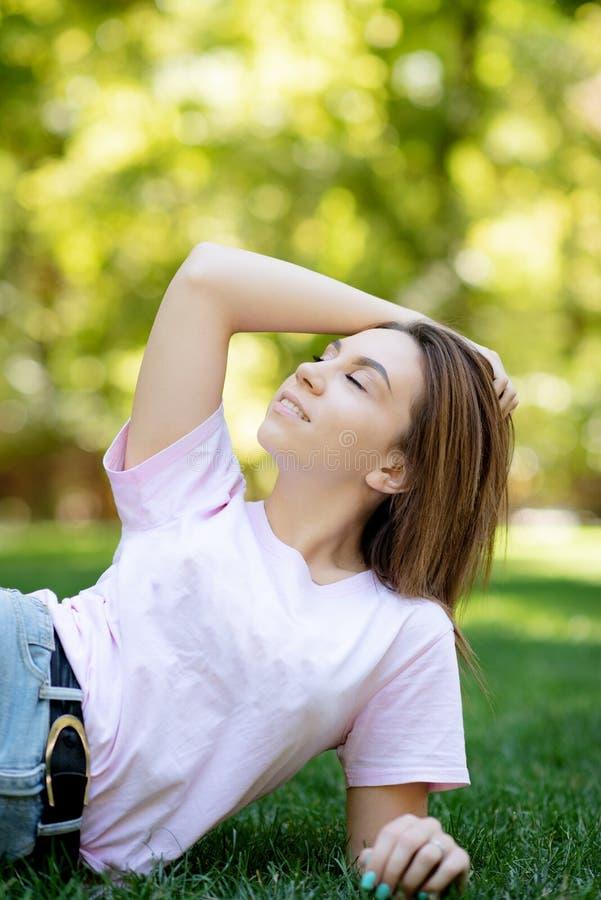 Mulher de sorriso bonita que encontra-se em uma grama exterior Está absolutamente feliz estilo de vida, férias de verão foto de stock royalty free
