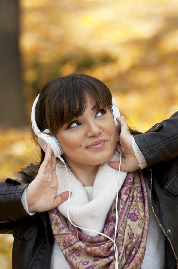 Mulher de sorriso bonita que escuta a música imagem de stock royalty free