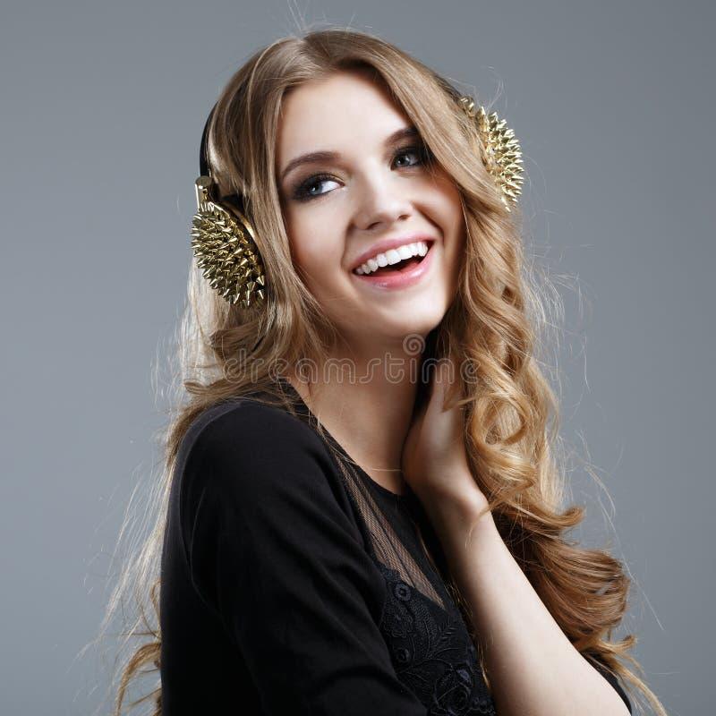 Mulher de sorriso bonita que escuta a música imagem de stock