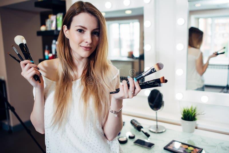Mulher de sorriso bonita que está com uma variedade de escovas da composição no estúdio da beleza fotografia de stock