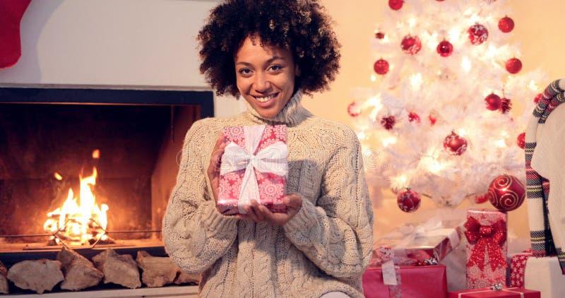 Mulher de sorriso bonita que guarda o presente encaixotado xmas imagem de stock