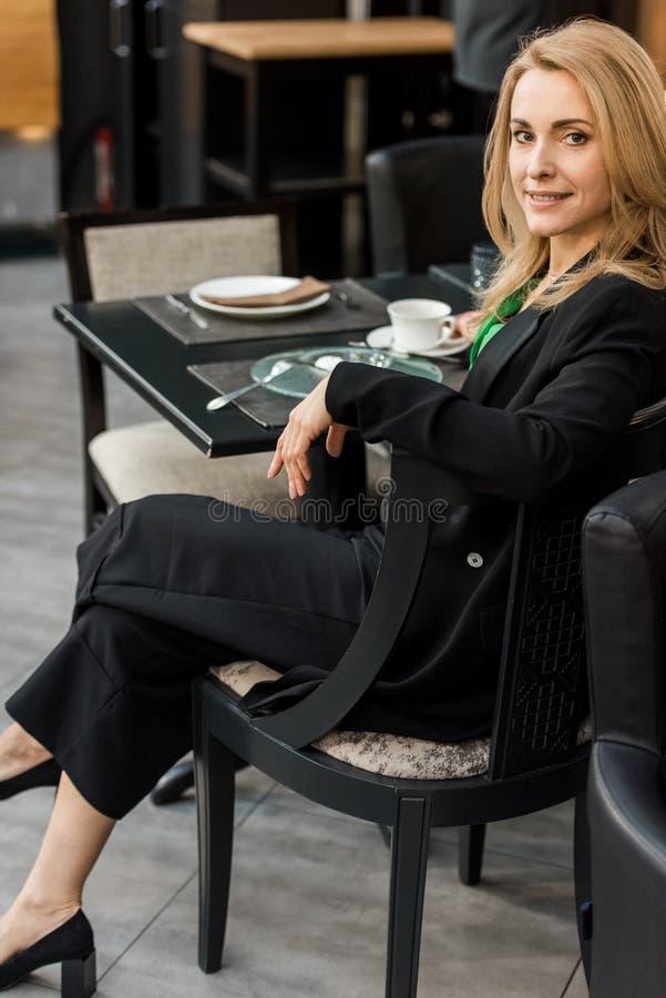 mulher de sorriso bonita que olha a câmera ao sentar-se na tabela imagem de stock