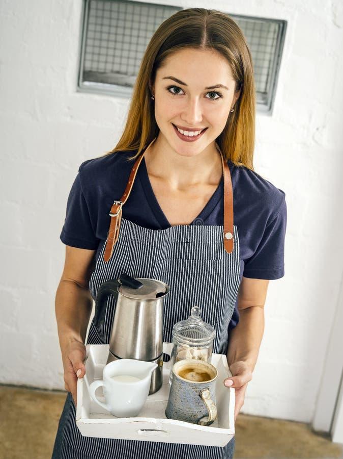 Mulher de sorriso bonita que serve o café imagens de stock
