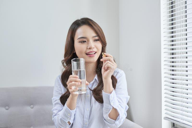 Mulher de sorriso bonita que toma o comprimido da vitamina Suplemento diet?tico imagem de stock