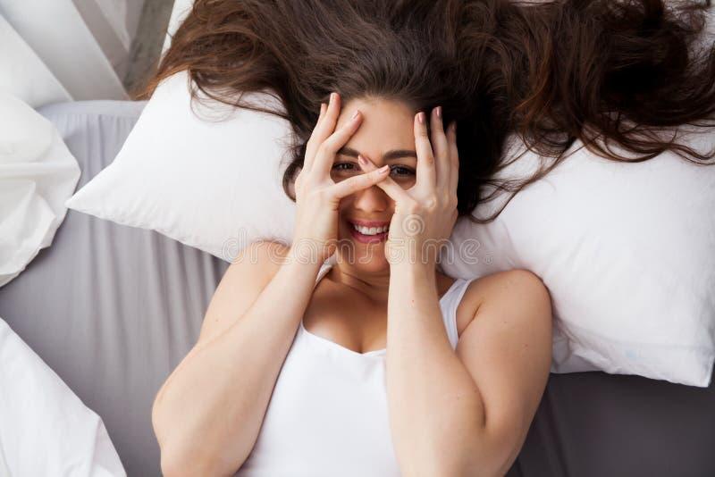 Mulher de sorriso caucasiano nova bonita que cobre seus olhos na cama imagem de stock