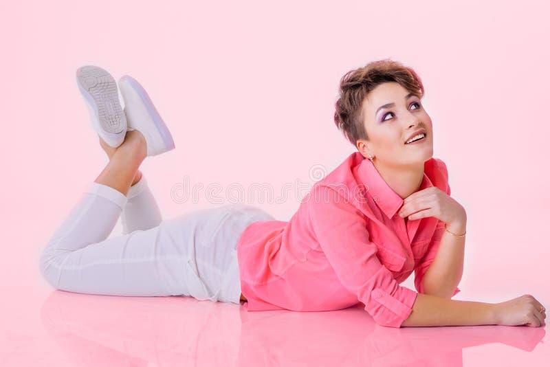 A mulher de sorriso coloca no assoalho na camisa cor-de-rosa e na vista em cima imagem de stock royalty free