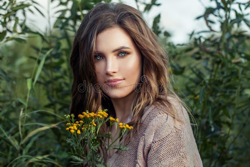 Mulher de sorriso com as flores amarelas do tansy no fundo da grama verde do verão imagem de stock royalty free