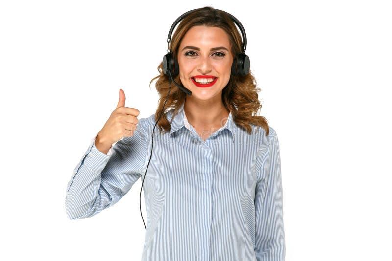 A mulher de sorriso com auriculares mostra o polegar fotografia de stock