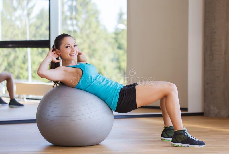 Mulher de sorriso com a bola do ajuste que dobra os músculos no gym foto de stock