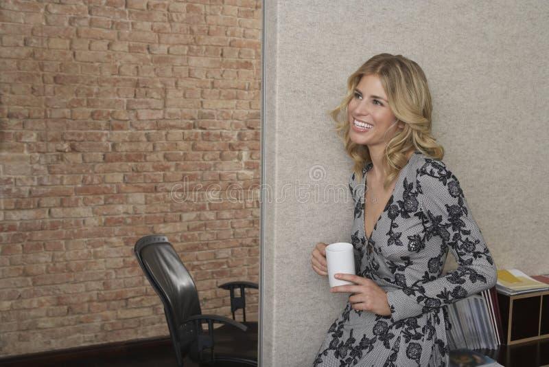 Mulher de sorriso com a caneca no escritório fotos de stock royalty free
