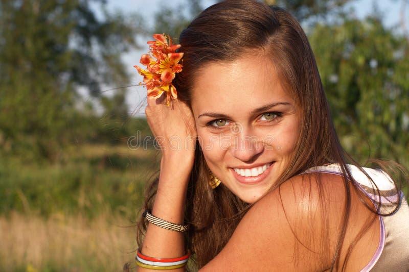 Mulher de sorriso com a flor no cabelo fotografia de stock