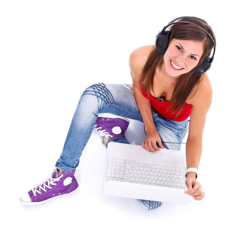 Mulher de sorriso com fones de ouvido e portátil fotos de stock