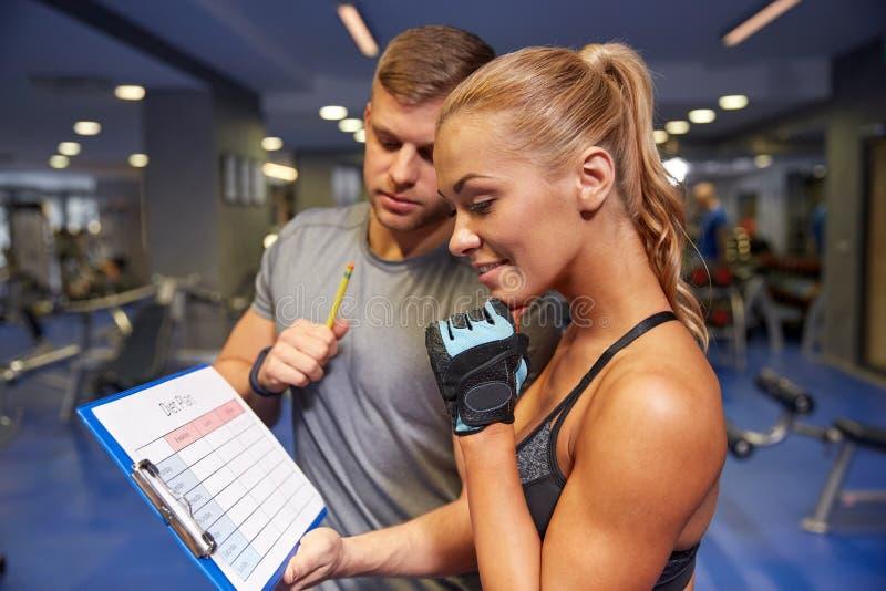 Mulher de sorriso com instrutor e prancheta no gym imagem de stock