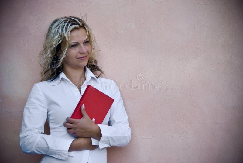 Mulher de sorriso com livro vermelho fotografia de stock royalty free